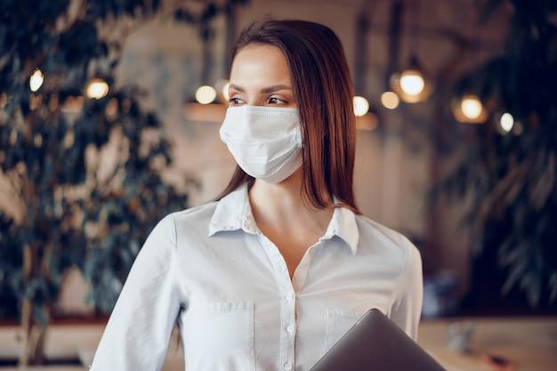 Giovane donna in piedi con maschera facciale e tenendo il computer portatile in ufficio