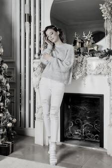Giovane donna in piedi davanti al camino e all'albero di natale con doni felici e sognanti. colore bianco argento sullo sfondo del soggiorno in occasione di buon natale e felice anno nuovo. momenti d'atmosfera in famiglia