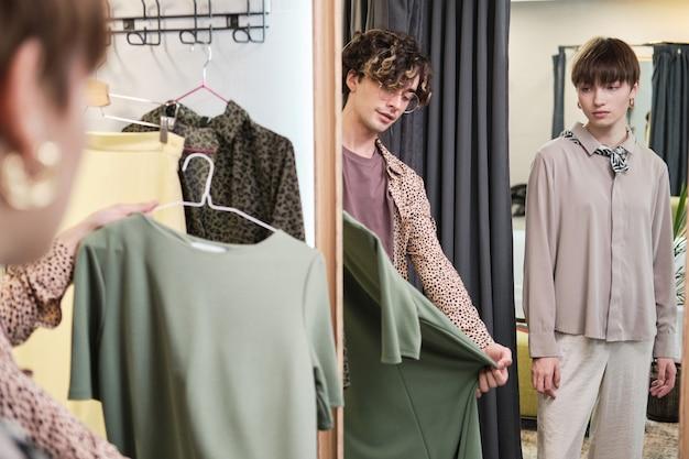 Giovane donna in piedi nel camerino del negozio mentre lo stilista le suggerisce nuovi vestiti