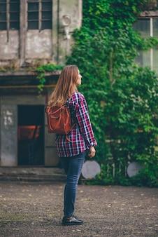 Giovane donna in piedi di fronte al vecchio edificio e guardando il panorama
