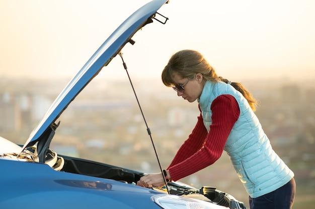 Giovane donna in piedi vicino a un'auto in panne con il cofano sollevato che ha problemi con il suo veicolo.