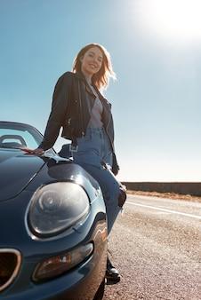 Giovane donna in piedi vicino a un'auto senza tetto in giacca di pelle