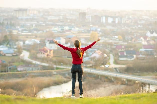 Giovane donna in piedi all'aperto alzando le mani godendo della vista sulla città