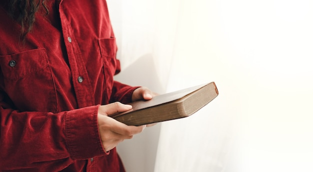 Una giovane donna in piedi e pregando sulla bibbia, copia dello spazio. accanto alla finestra a specchio