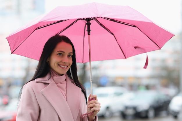 Giovane donna in piedi sotto la pioggia con l'ombrello in mano. concetto di previsioni del tempo