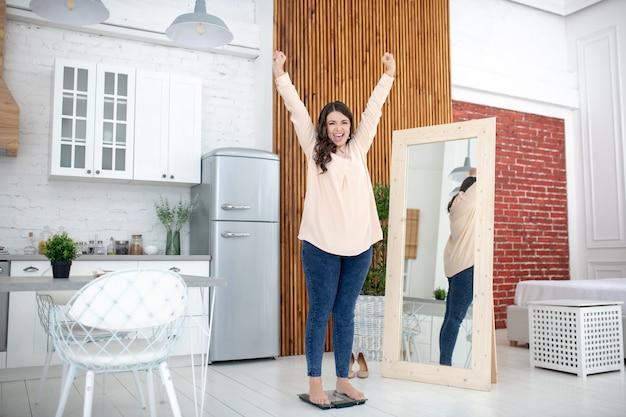 Giovane donna in piedi su una bilancia e sentirsi benissimo