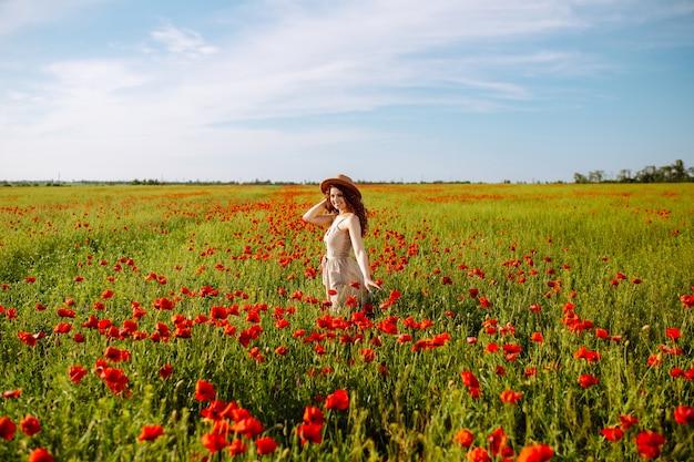 Una giovane donna si trova in un bellissimo giardino fiorito con fiori rossi.
