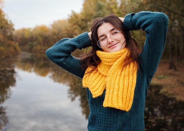 Giovane donna si trova su un ponte nella foresta autunnale moda autunnale