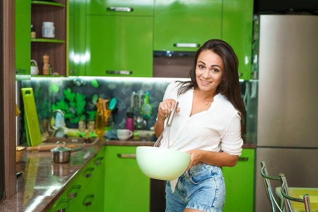 La giovane donna sta in cucina e sbatte in un piatto caucasica ragazza felice in abiti casual prepara...