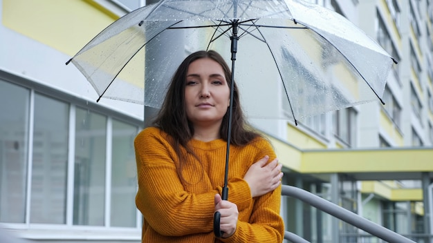 La giovane donna sta sotto un ombrello trasparente sotto la pioggia quando fa freddo, al rallentatore