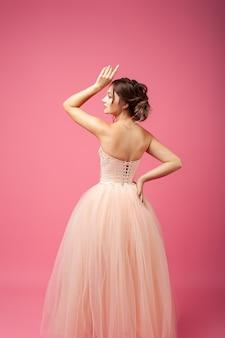 Una giovane donna sta con la schiena su uno sfondo isolato una bellissima modella in un beige...