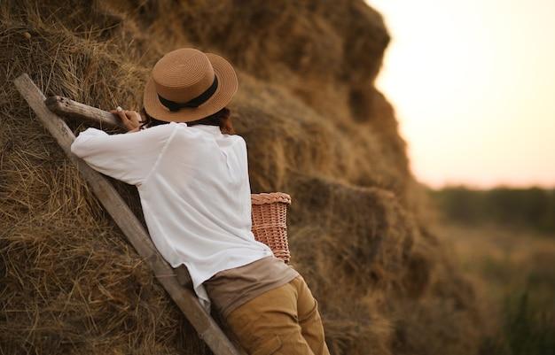 Giovane donna si trova su una scala in legno con un cesto di vimini