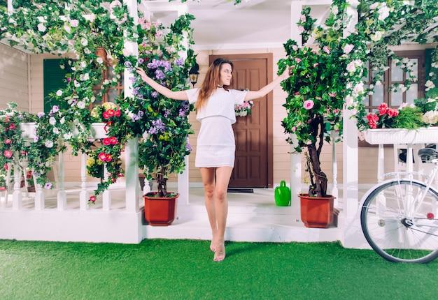 Giovane donna che sta davanti alla sua bella casa floreale