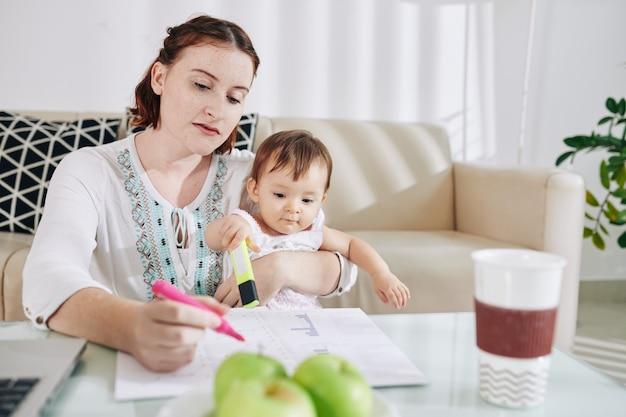 Giovane donna che rimane a casa con la piccola figlia e che evidenzia i dati nella relazione finanziaria per il suo lavoro