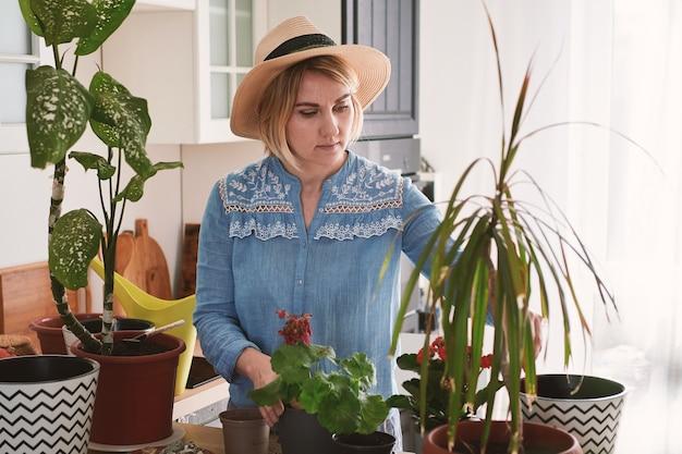 Giovane donna in un cappello di paglia che cresce e pianta i fiori domestici
