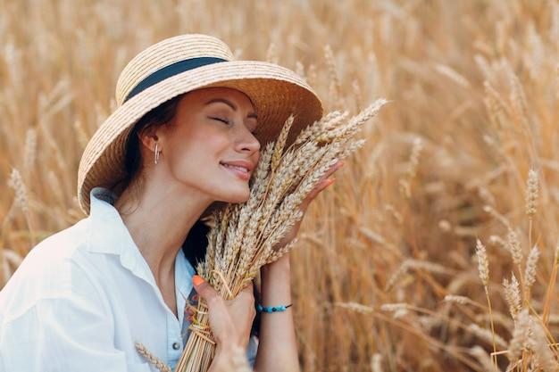 Giovane donna in cappello di paglia che tiene un covone di spighe di grano al campo agricolo
