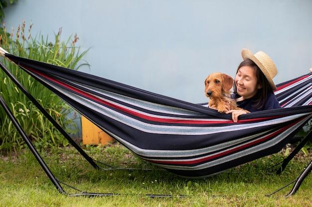 Giovane donna in cappello di paglia seduto in amaca con piccolo bassotto marrone a pelo duro in una giornata estiva