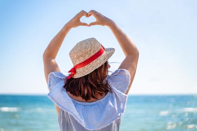 La giovane donna in un cappello di paglia e una vista delle spalle del vestito da estate fa il segno di amore con le sue mani sul mare blu