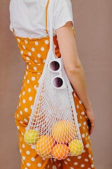 Giovane donna in cappello di paglia con un sacchetto a rete di frutta. stile di vita sostenibile. concetto senza plastica.