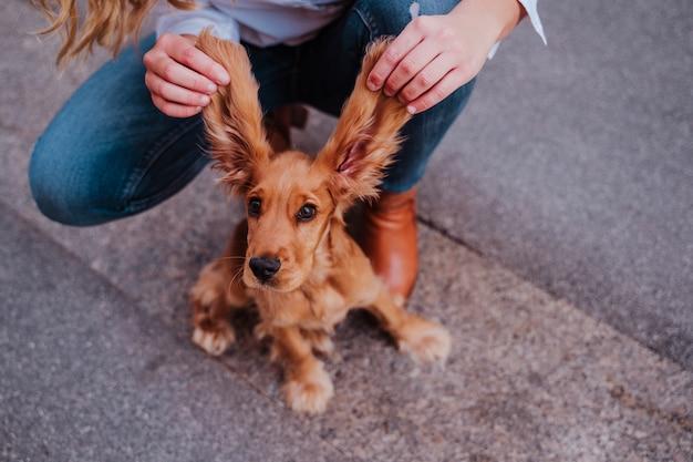 Giovane donna alla strada che tiene le orecchie grandi divertenti del suo simpatico cane cocker. stile di vita all'aperto con animali domestici