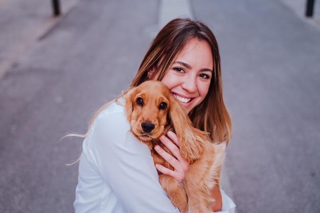 Giovane donna alla strada tenendo con il suo simpatico cane cocker sulla spalla. stile di vita all'aperto con animali domestici