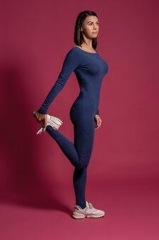 Giovane donna che allunga i muscoli delle gambe sulla superficie marrone rossiccio