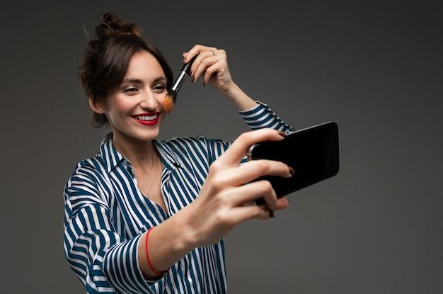 Giovane donna in blusa a strisce che sorride e che utilizza cellulare nero invece dello specchio e che mette sul trucco con la spazzola isolata