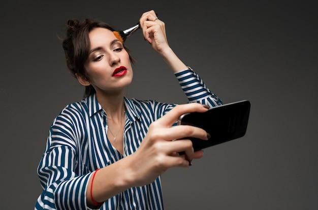 Giovane donna in blusa a strisce usando il cellulare nero invece dello specchio e mettendo su polvere con la spazzola di trucco isolata