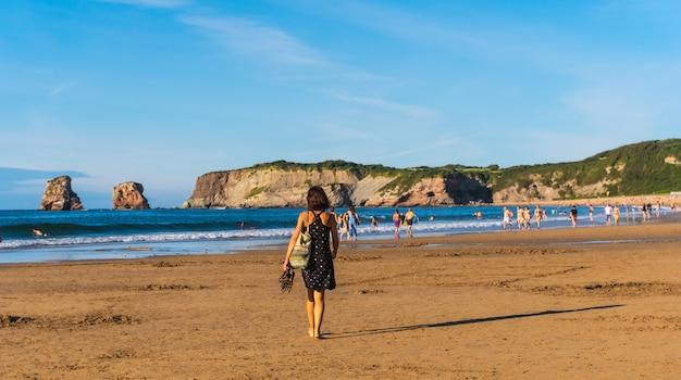 Una giovane donna che passeggia lungo la spiaggia di hendaye, nei paesi baschi francesi