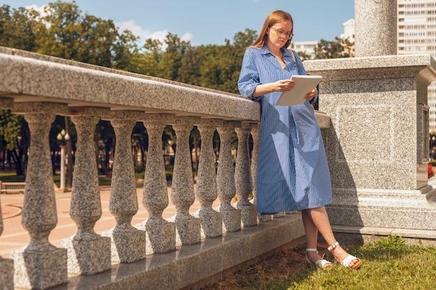 Giovane studentessa in piedi vicino all'università e leggendo il libro di testo che si prepara per l'esame