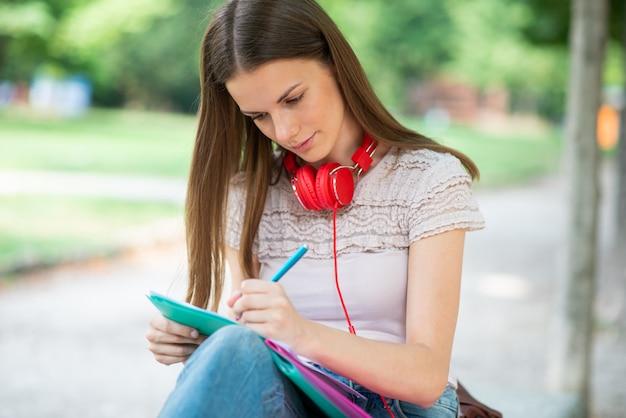 Studio della studentessa della giovane donna all'aperto davanti alla sua scuola