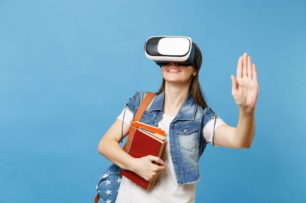 La giovane studentessa in cuffia per la realtà virtuale tiene i libri toccando qualcosa come premere il pulsante, indicando lo schermo virtuale mobile isolato su sfondo blu. istruzione nel college universitario scolastico.