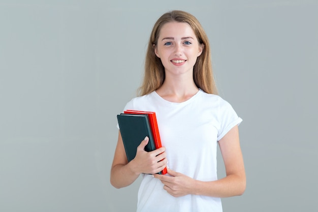 Studente della giovane donna con i libri, manuali in mani, isolate su gray
