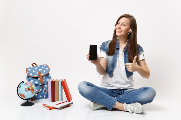 La giovane studentessa con il telefono cellulare degli auricolari con lo schermo vuoto nero in bianco ascolta la musica mostra il pollice in su vicino ai libri dello zaino del globo isolati sul muro bianco