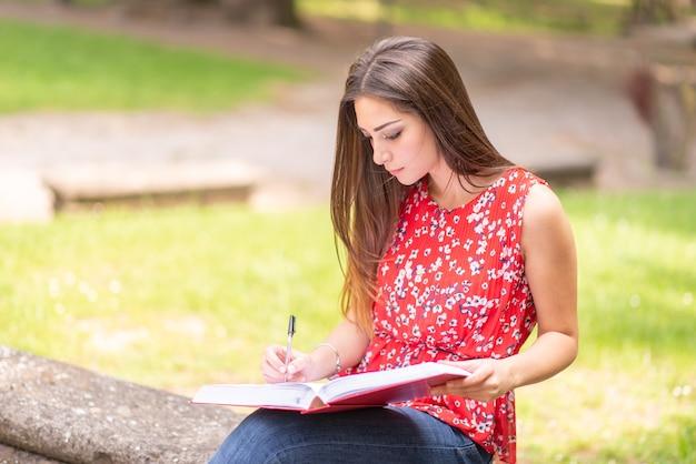 Studente della giovane donna che scrive su un libro all'aperto in un parco