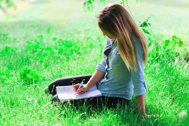 Giovane donna che studia nel parco