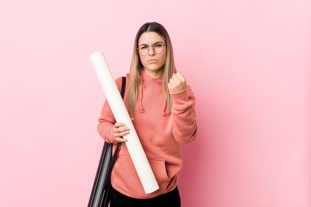 Giovane donna che studia architettura che mostra il pugno alla macchina fotografica, espressione facciale aggressiva.