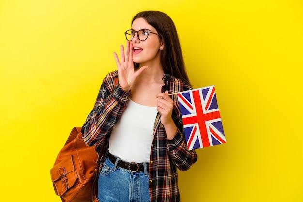 Giovane donna che studia inglese isolato su sfondo rosa gridando e tenendo il palmo vicino alla bocca aperta.