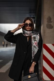 Giovane donna in elegante sciarpa di seta sulla testa in occhiali da sole alla moda in cappotto vintage nero con borsa in pelle in posa all'aperto in città. la modella alla moda della ragazza sta vicino alla colonna a strisce. stile retrò