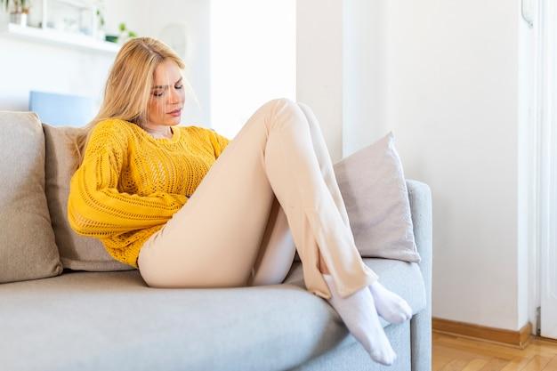 Giovane donna che soffre di dolori addominali mentre è seduta sul letto di casa. giovane donna che soffre di dolori addominali a casa. concetto di ginecologia. giovane donna dolorante sdraiata sul divano a casa