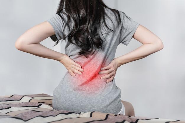 Giovane donna che soffre di mal di schiena sul letto dopo il risveglio