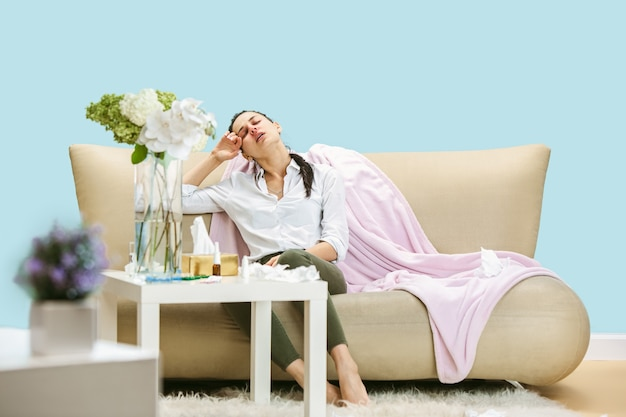 Giovane donna che soffre di polvere domestica o allergia stagionale. starnutire nel tovagliolo e sedersi circondato da tovaglioli usati sul pavimento e sul divano. assunzione di farmaci senza risultato. concetto di assistenza sanitaria.