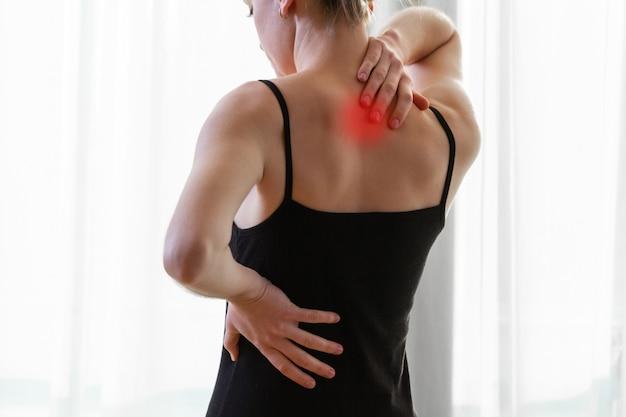 Giovane donna che soffre di dolore al collo e mal di schiena, allungando i muscoli a casa. donna dolore alla schiena e al collo