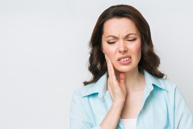 Giovane donna che soffre di un forte dolore ai denti che tocca la guancia con il concetto di odontoiatria della mano