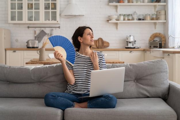 La giovane donna soffre di un colpo di calore piatto senza condizionatore d'aria che ondeggia il ventilatore seduto sul divano di casa