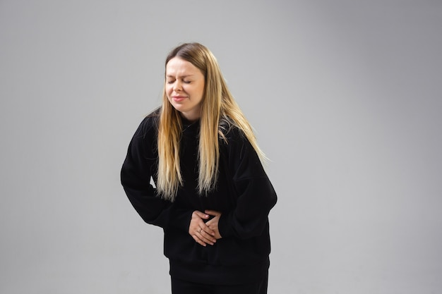 La giovane donna soffre di dolore si sente ammalata e la debolezza è isolata sul muro