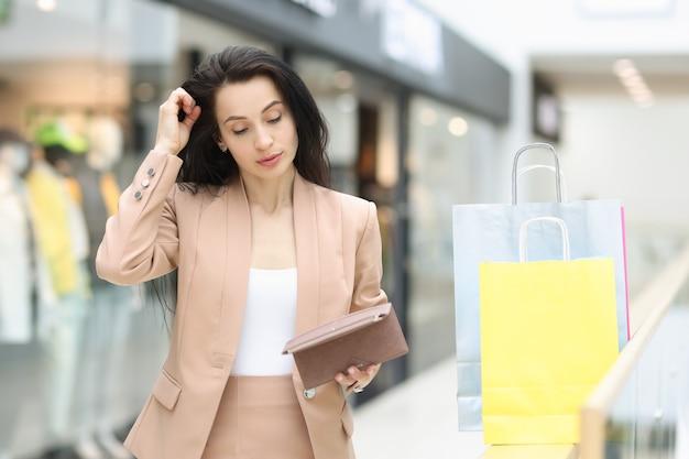 Giovane donna in vestito che esamina portafoglio vuoto nel centro commerciale