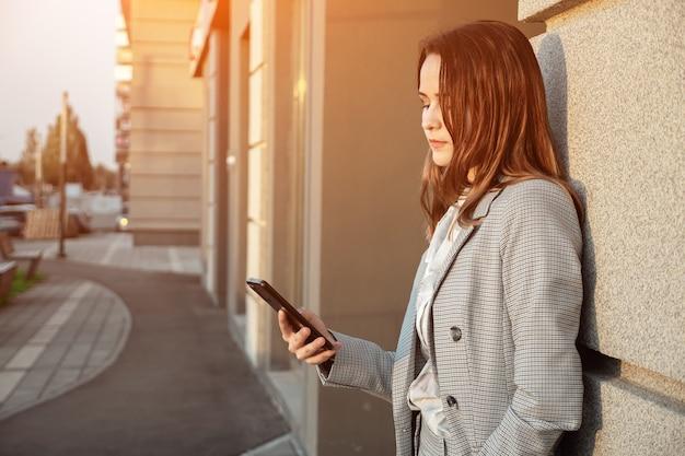 La giovane donna in un vestito guarda il telefono sulla strada vicino all'edificio