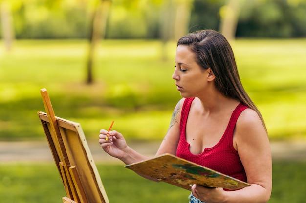 Giovane donna in abiti estivi dipinto su una tela in piedi in un parco.