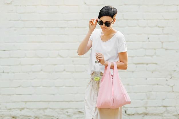 Giovane donna in abiti estivi con una borsa ecologica e una bottiglia d'acqua riutilizzabile. stile di vita sostenibile. concetto ecologico.